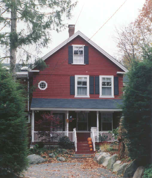 A red house with dark blue window shutters